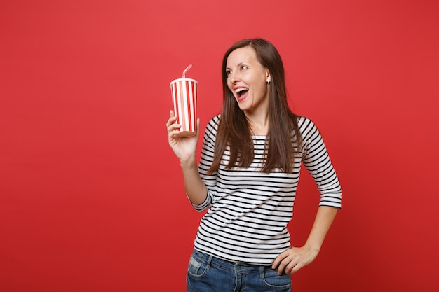 Cheerful young woman holding plastic cup of cola or soda, looking aside, keeping mouth wide open isolated on bright red wall background. people sincere emotions, lifestyle concept. mock up copy space.