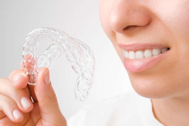 Cheerful young woman holding plastic transparent braces