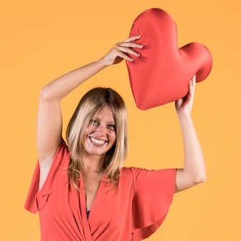 Cheerful young woman holding red heart cushion in hand