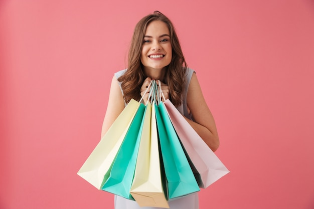 Cheerful young woman holding shopping bags.