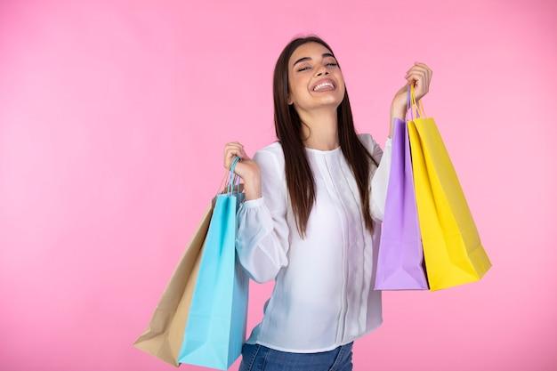元気な若い女性は、購入したバッグを持っています。カラフルな買い物袋を持つ楽しいトレンディな女の子