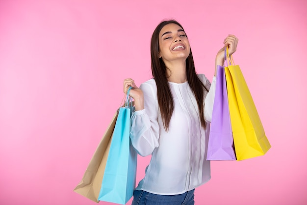 Cheerful young woman holds bags with a purchases. joyful trendy girl with a colorful shopping bags