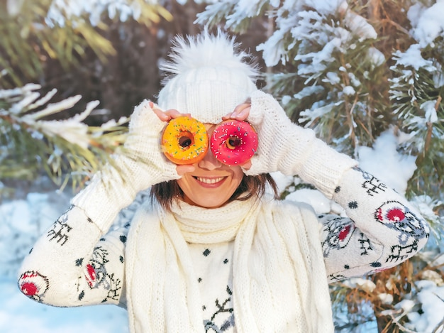 Cheerful young woman holds donuts in her hands in the winter forest, concept of winter holiday