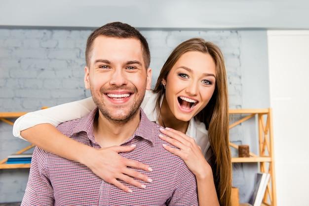 Веселая молодая женщина обнимает своего парня