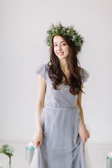Веселая молодая женщина в сером вечернем платье и венке из сосны и эвкалипта на голове позирует