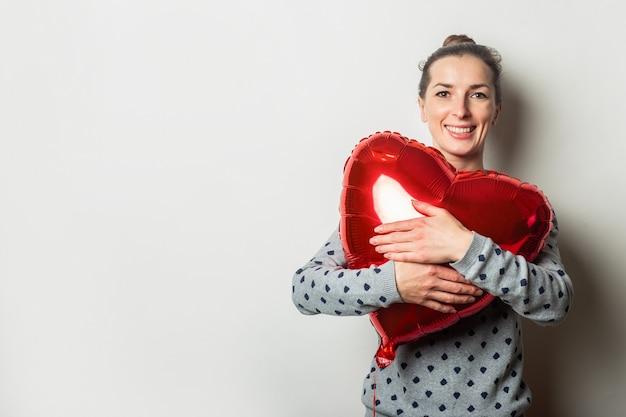 セーターを着た陽気な若い女性は、明るい背景に気球の心を抱きしめます。バレンタインデーのコンセプト。愛する人を探しましょう。
