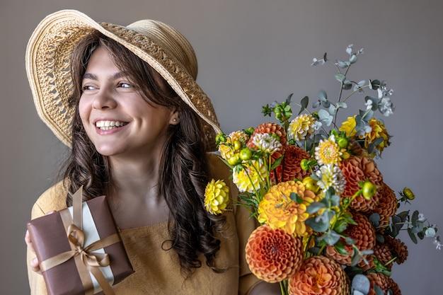 밝은 국화 꽃다발과 회색 배경에 선물을 들고 노란 드레스와 모자를 쓴 쾌활한 젊은 여성.