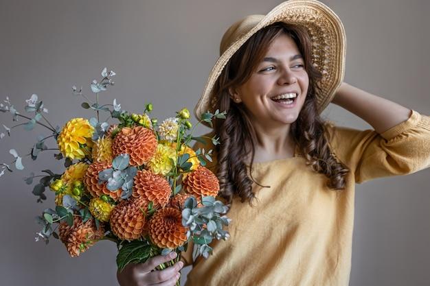 회색 배경에 밝은 국화 꽃다발을 든 노란 드레스와 모자를 쓴 쾌활한 젊은 여성.