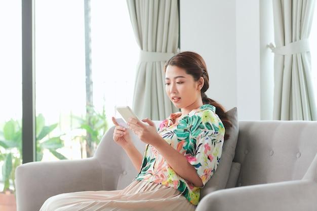 カジュアルな服装の陽気な若い女性が自宅のリビングルームで時間を過ごしてソファに座っています。