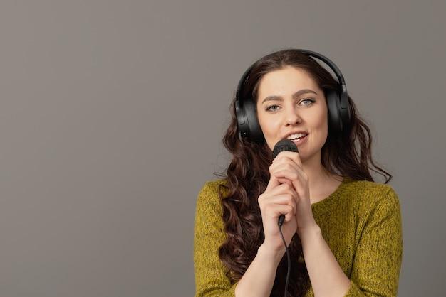 헤드폰 캐주얼 옷에 쾌활 한 젊은 여자는 마이크에 노래를 노래