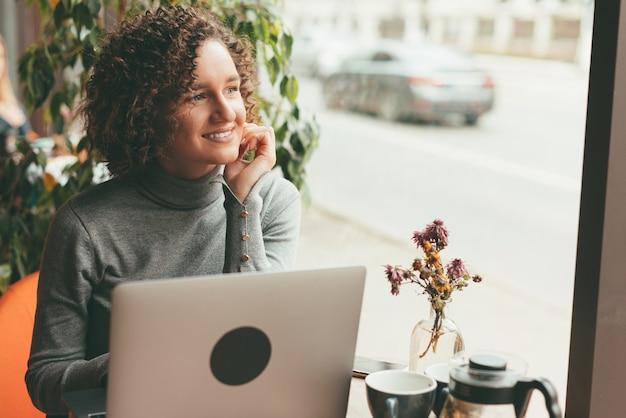 ノートパソコンの近くのカフェに座って笑顔でカジュアルに陽気な若い女性