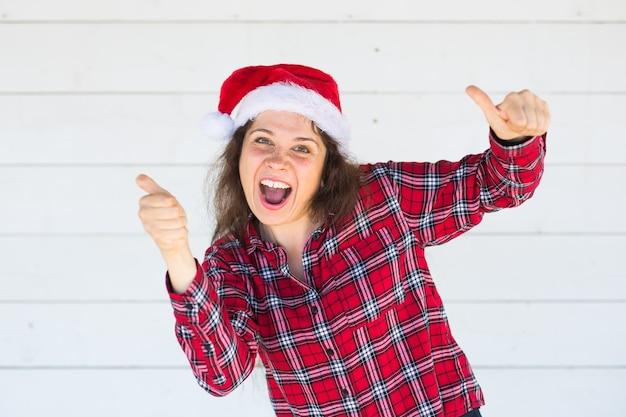 白いスペースに親指を示すクリスマス帽子の陽気な若い女性
