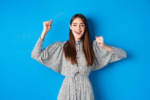 手を上げて笑顔のドレスを着た陽気な若い女性