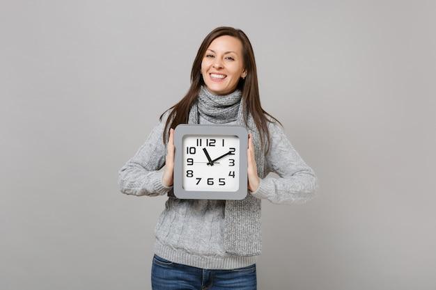 Веселая молодая женщина в сером свитере, шарфе удерживайте квадратные часы, изолированные на сером фоне, студийный портрет. здоровый образ жизни моды, искренние эмоции людей, концепция холодного сезона. копируйте пространство для копирования.
