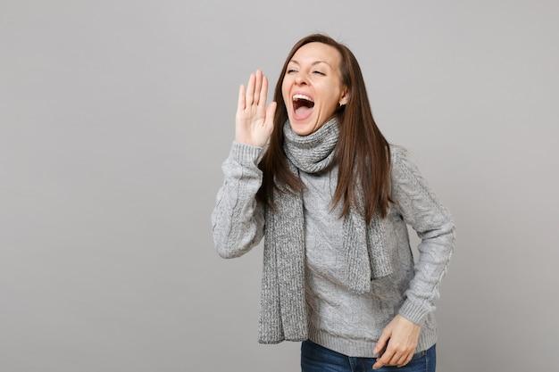 灰色のセーター、灰色の壁の背景に分離された手のジェスチャーで叫んでスカーフの陽気な若い女性。健康的なファッションライフスタイル、人々の誠実な感情、寒い季節のコンセプト。コピースペースをモックアップします。