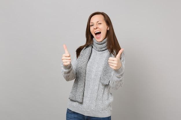 Веселая молодая женщина в сером свитере, шарфе показывает палец вверх, мигает изолированной на сером стенном фоне. здоровый образ жизни моды, искренние эмоции людей, концепция холодного сезона. копируйте пространство для копирования.