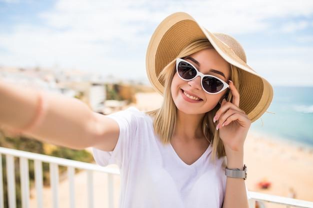 夏のリゾートの海で携帯電話でselfieを取る帽子とサングラスの陽気な若い女性
