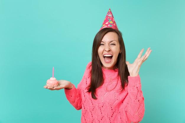 분홍색 스웨터를 입은 쾌활한 젊은 여성, 생일 모자에 촛불이 든 케이크를 들고, 손을 펼치고, 파란 벽 배경에 고립되어 비명을 지르고 있습니다. 사람들이 라이프 스타일 개념입니다. 복사 공간을 비웃습니다.