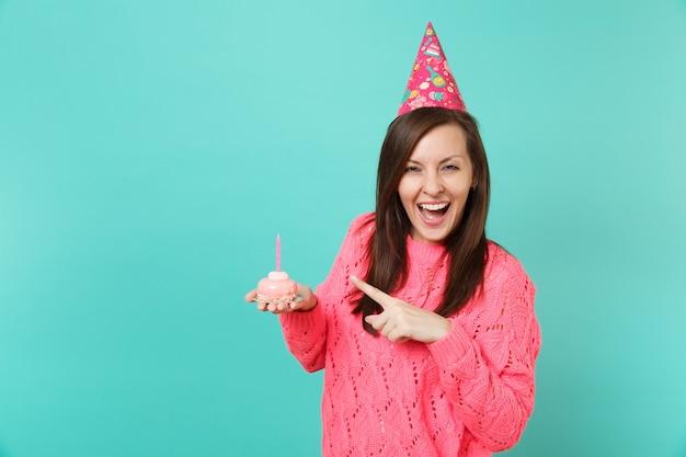 분홍색 스웨터를 입은 쾌활한 젊은 여성, 파란색 배경 스튜디오 초상화에 격리된 손에 촛불을 들고 케이크에 검지 손가락을 가리키는 생일 모자. 사람들이 라이프 스타일 개념입니다. 복사 공간을 비웃습니다.