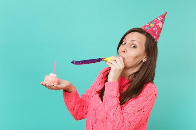 분홍색 스웨터를 입은 쾌활한 젊은 여성, 파란색 청록색 벽 배경에 격리된 촛불을 들고 손으로 케이크를 들고 파이프를 연주하는 생일 모자. 사람들이 라이프 스타일 개념입니다. 복사 공간을 비웃습니다.