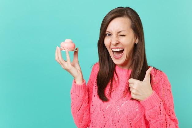 Веселая молодая женщина в вязаном розовом свитере мигает, показывая большой палец вверх, держа в руке торт, изолированный на синем бирюзовом стенном фоне, студийный портрет. концепция образа жизни людей. копируйте пространство для копирования.