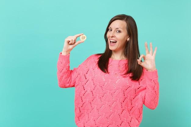 분홍색 스웨터를 입은 쾌활한 젊은 여성이 ok 제스처를 보여주고 파란색 청록색 벽 배경에 격리된 미래 통화인 비트코인을 손에 들고 있습니다. 사람들이 라이프 스타일 개념입니다. 복사 공간을 비웃습니다.
