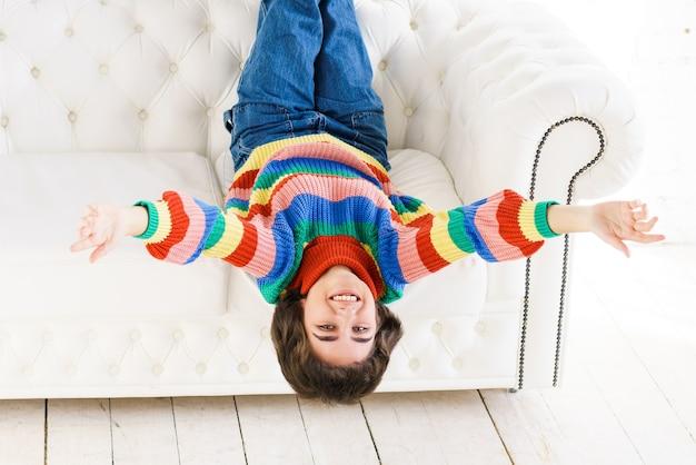レインボーセーターを着た元気な若い女性がソファに横になり、頭を下げて腕を横に伸ばして...