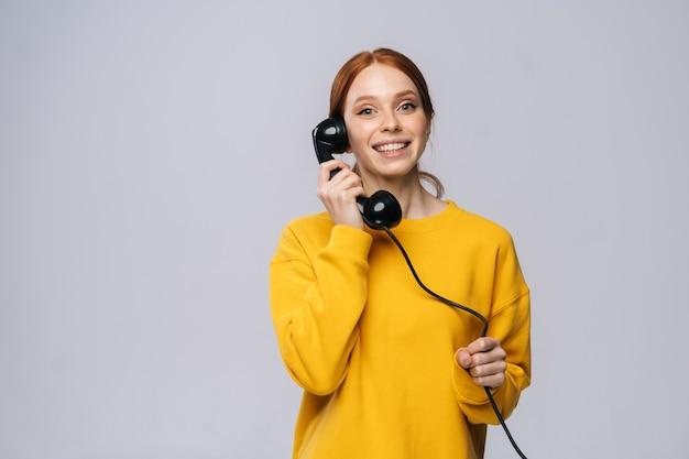 Веселая молодая женщина в стильном желтом свитере разговаривает по ретро-телефону и смотрит в камеру
