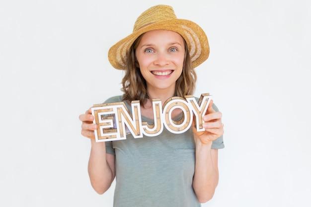 Жизнерадостная молодая женщина в удерживании соломенной шляпы лета наслаждается словом