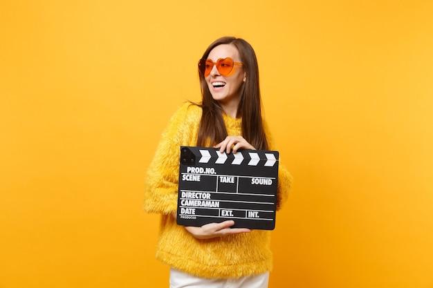 黄色の背景で隔離のカチンコを作る古典的な黒いフィルムを保持して脇を探しているセーターオレンジ色のハートの眼鏡の陽気な若い女性。人々は誠実な感情のライフスタイル。広告エリア。