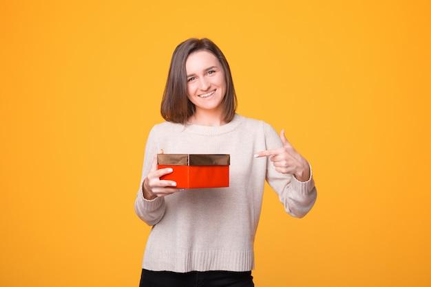 노란색 배경 위에 빨간색 선물을 가리키는 스웨터에 쾌활 한 젊은 여자