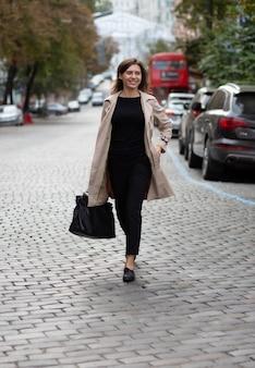 Веселая молодая женщина в модном наряде пересекает городскую улицу. снимок в полный рост