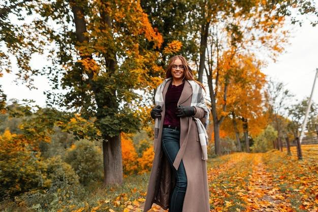 트렌디 한 따뜻한 가을 옷을 입은 쾌활한 젊은 여성이 노란색-주황색 잎이있는 나무가있는 공원에서 경로를 따라 실행됩니다. 긍정적 인 미소를 지닌 명랑 소녀가 주말을 즐기고 있습니다.