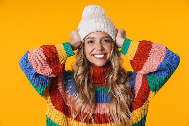Веселая молодая женщина в зимней шапке и свитере, улыбаясь в камеру, изолированную над желтой стеной