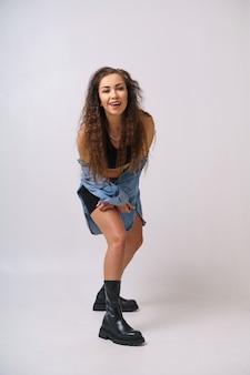 陽気な若い女性がデニムジャケットと黒のスポーツショーツで明るい背景で踊っていて...
