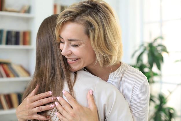 쾌활한 젊은 여성이 거실에서 중년의 어머니를 껴안고 있습니다.