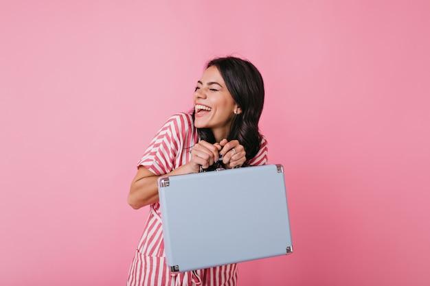 쾌활한 젊은 여자가 재미 있고 진정으로 웃고 있습니다. 소녀는 다른 사람의 파란색 가방을 가지고 장난을칩니다.