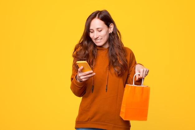 Веселая молодая женщина смотрит и улыбается по телефону и держит сумку для покупок