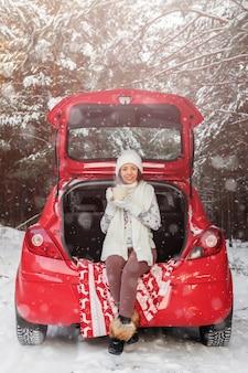 쾌활한 젊은 여성은 겨울에 숲 속의 열린 트렁크에 앉아 머그, 겨울 크리스마스, 새해 여행 또는 휴가에서 뜨거운 음료를 마시고 있습니다