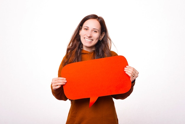 Cheerful young woman is smiling at the camera and holding a speech bubble near a white wall