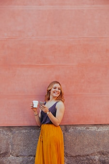 Cheerful young woman isolated on a wall using her phone