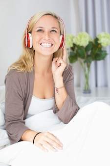 Cheerful young woman listening music or audiobook