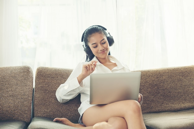 Cheerful young woman listening to music from earphones while holding laptop