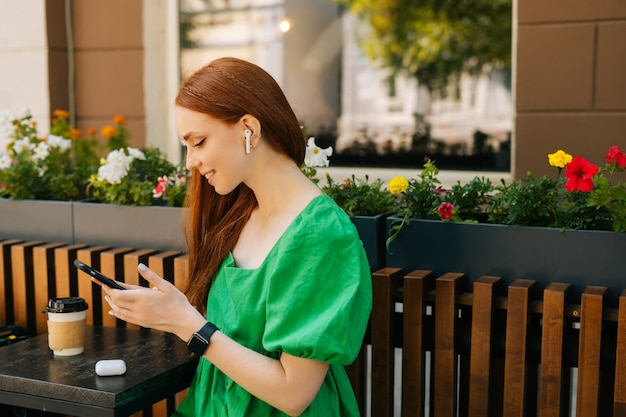 テーブルに座って携帯電話とワイヤレスヘッドフォンを使用して音楽を聴いて陽気な若い女性