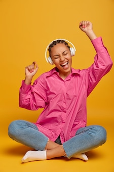 Cheerful young woman listens audio track in headphones, raises arms, sits in lotus pose against yellow wall, moves with rhythm of music, full of energy, feels happy and relaxed. people, leisure