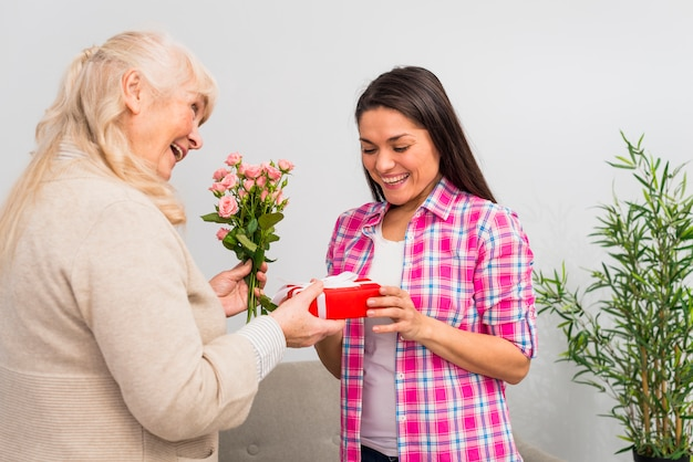 Cheerful young woman looking at red gift box given by her senior mother