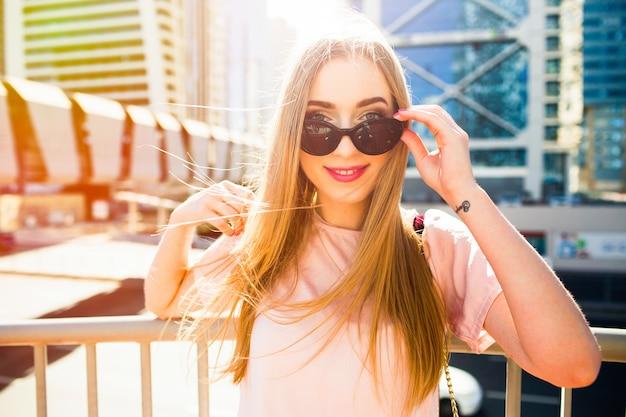 Giovane donna allegra guarda sopra gli occhiali da sole che presentano sotto il