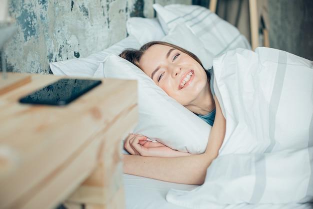 그녀의 침대에 부드러운 베개에 누워 웃 고 쾌활 한 젊은 여자. 그녀의 침대 근처 테이블에 스마트폰