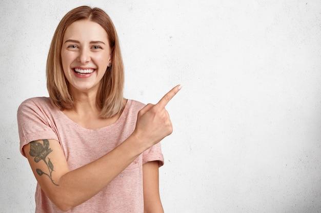 Веселая молодая модель женщины с короткой прической, зубастой улыбкой указывает в верхнем правом углу, одетая в повседневную одежду