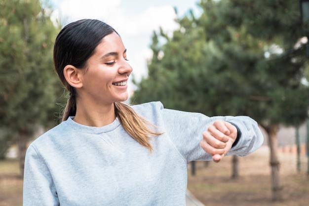 Жизнерадостная молодая женщина контролируя ее жизненно важные показатели на умном диапазоне фитнеса. держать свое тело в хорошей форме